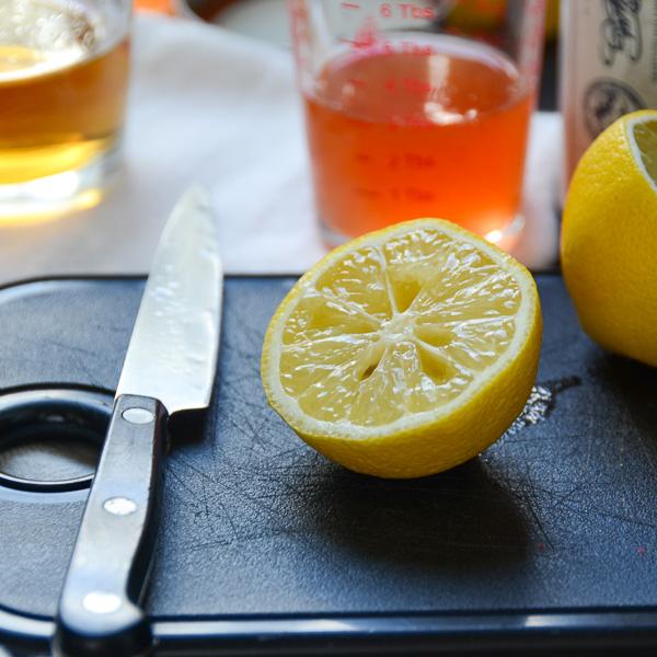 half a lemon on a cutting board with a sharp knife.