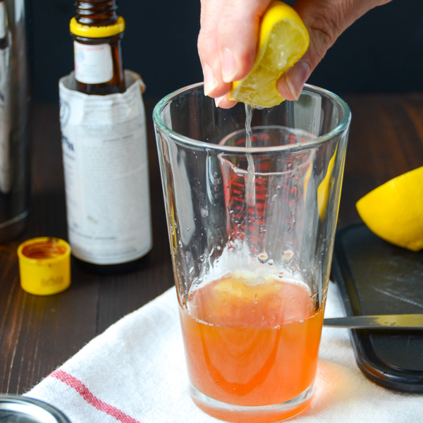 squeezing lemon into the glass.