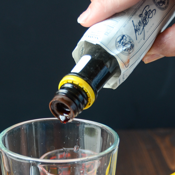 adding bitters to the glass.