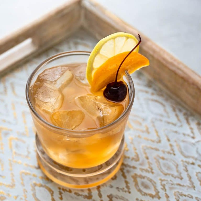 whiskey sour with peach, lemon and cherry garnish.
