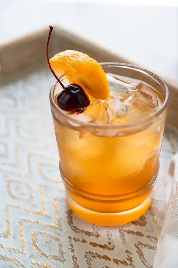 Peach Bourbon Sour on a tray.