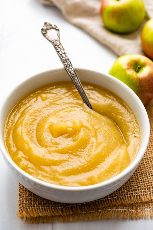 A bowl of applesauce with apples in the background.