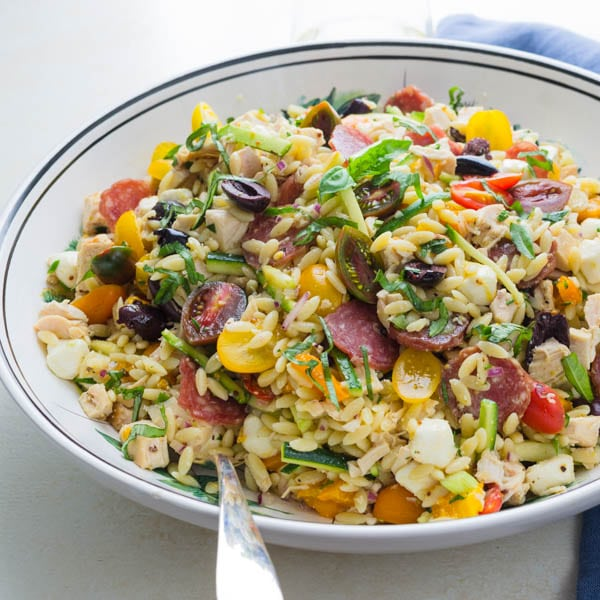 Lemony Chicken and Orzo Salad with a serving spoon and napkin.