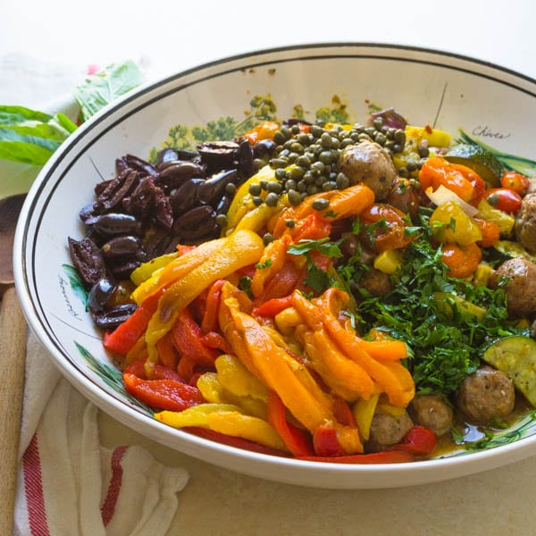 a large bowl of roasted vegetables, capers, olives and herbs.