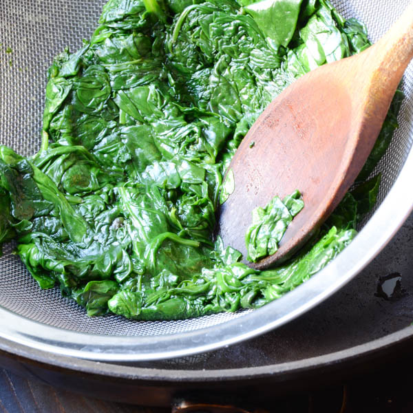 pressing out excess liquid from spinach