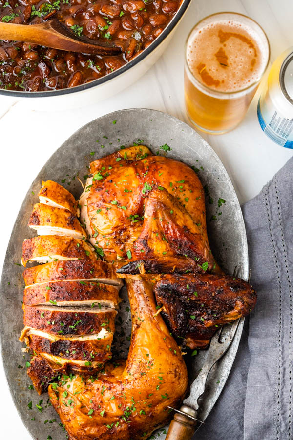 carving the bbq beer can chicken and serving on a platter.