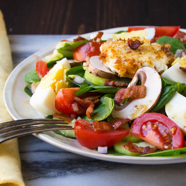 classic spinach salad on a plate with a fork and napkin.