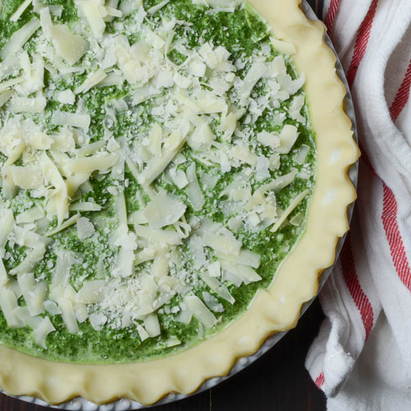 sprinkled cheese on spinach quiche.