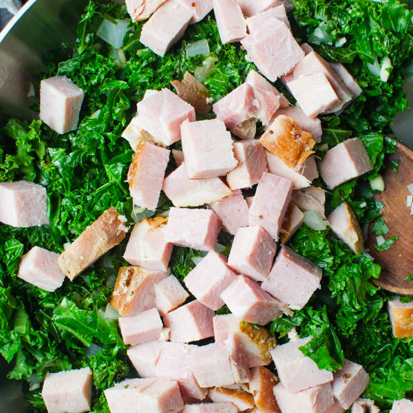 adding chunks of ham to the greens.