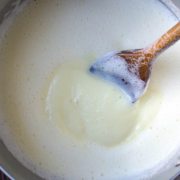 stirring custard with wooden spoon