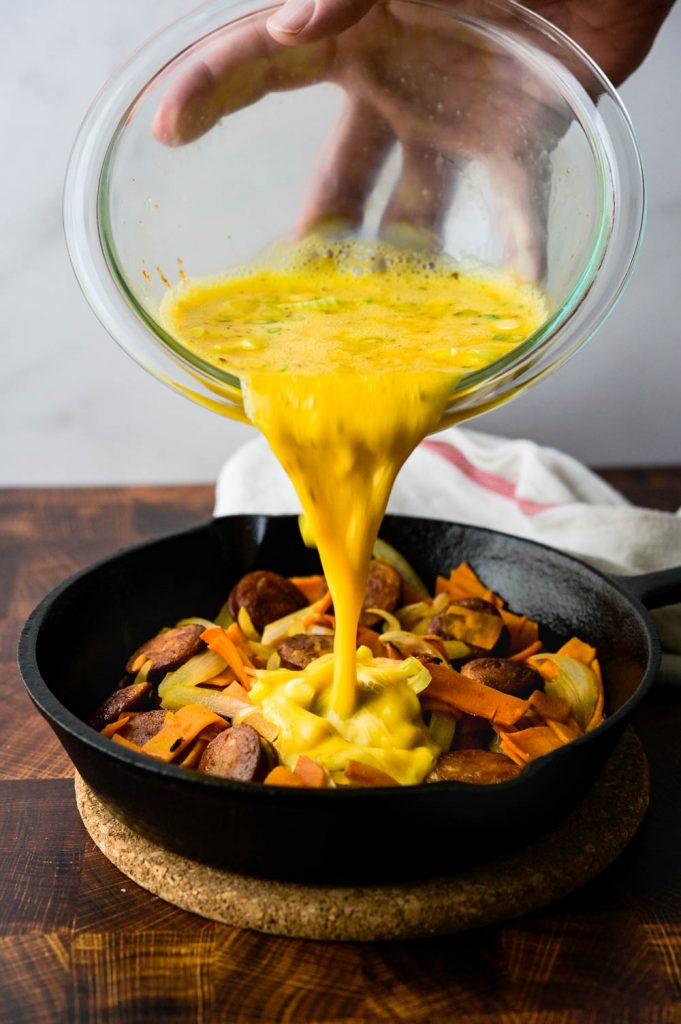 pouring egg mixture over sweet potatoes and sausage for frittata.