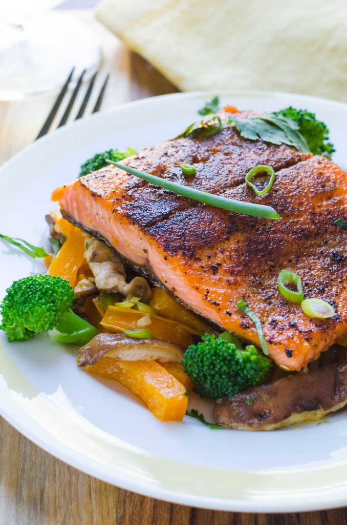 Asian salmon recipe with stir fried veggies on a plate with green onion and cilantro garnish.