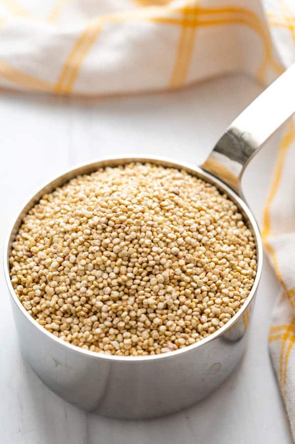uncooked quinoa in a measuring cup for edamame quinoa salad.