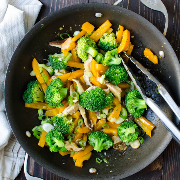 veggies in a pan with tongs