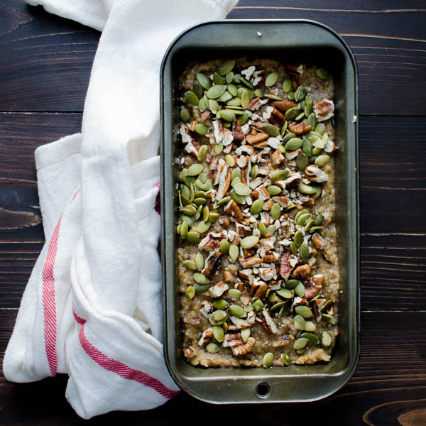 Gluten-Free Banana Coconut Bread batter in pan with nuts and seeds