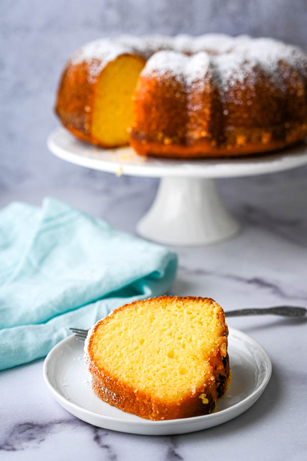 A slice of cake on a plate with the whole passion fruit cake in the background. This rum bundt cake is amazing.