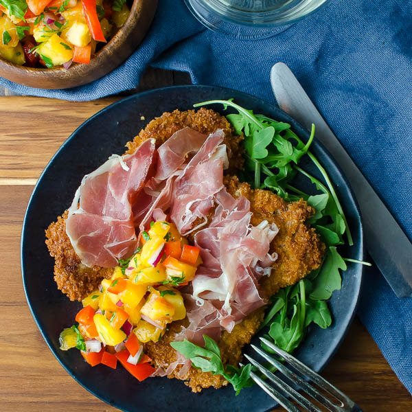 Crispy Pork Cutlets with Fresh Peach Salsa with fork and knife.