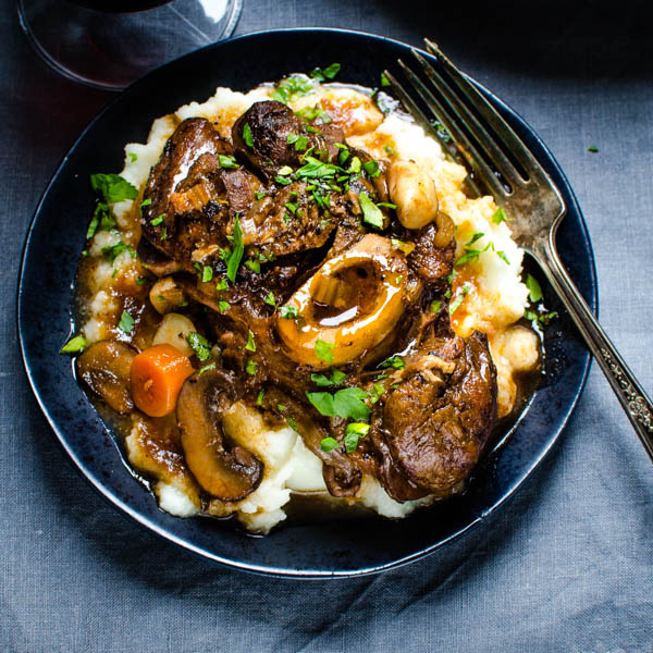 A serving of braised veal over mashed potatoes.