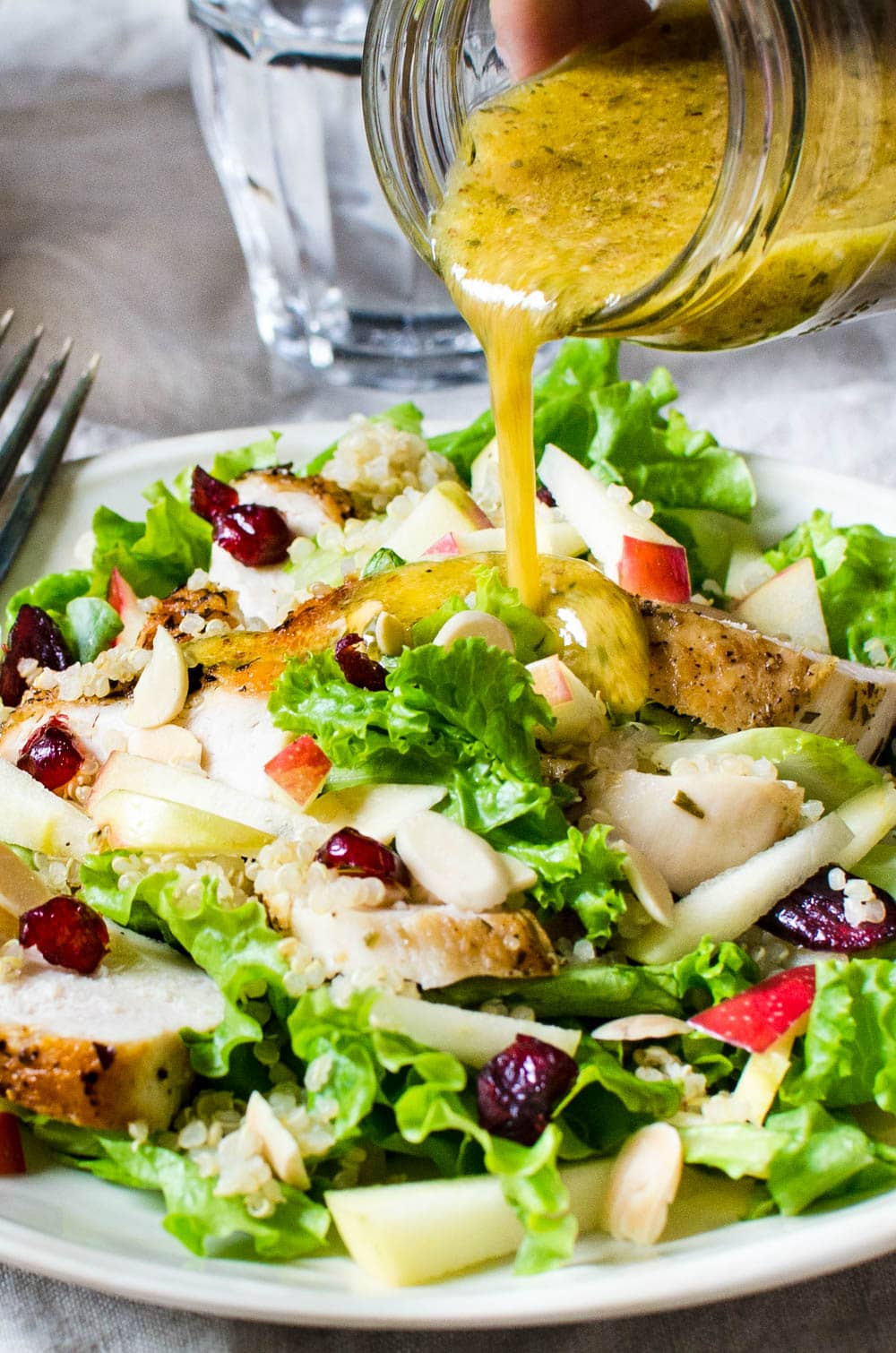 pouring dressing on the salad.