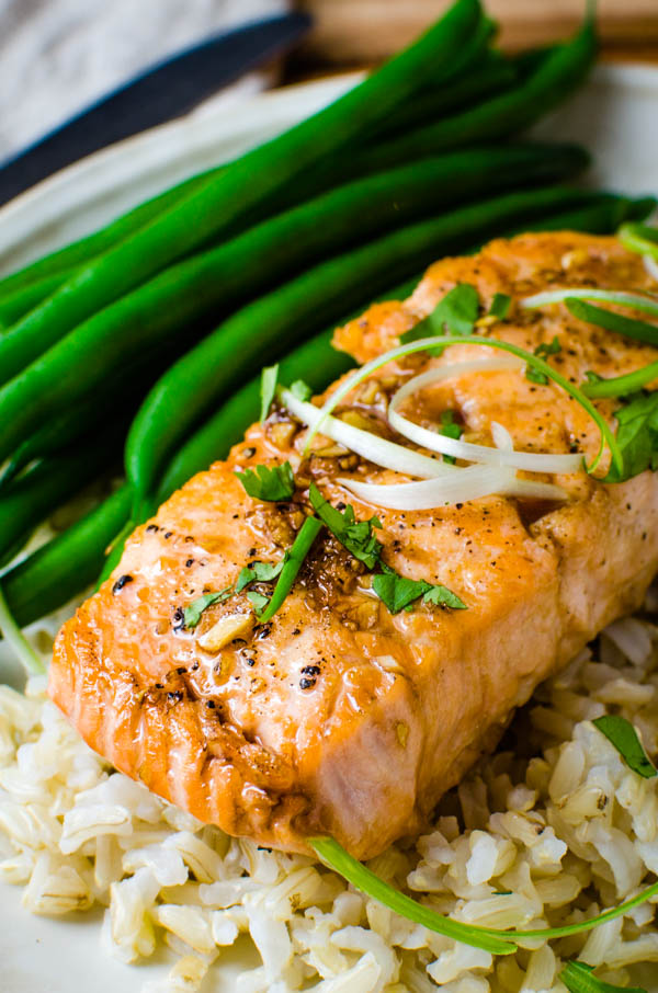 serving bourbon glaze on a piece of cooked salmon.