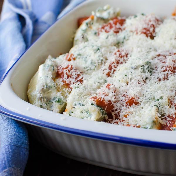 adding parmesan cheese to Mushroom Kale Stuffed Shells