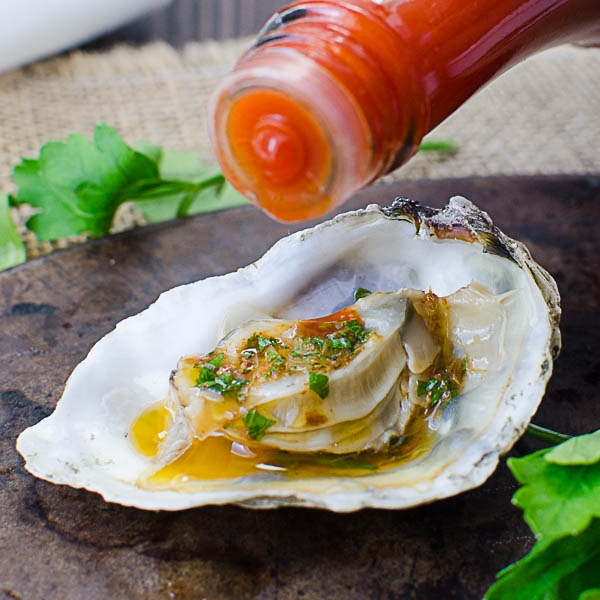 Adding Hot Sauce To Mardi Gras Grilled Oysters
