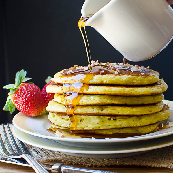 pouring syrup on Coconut Orange Buttermilk Pancakes