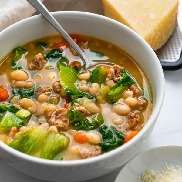 sausage white bean and escarole soup in a bowl.