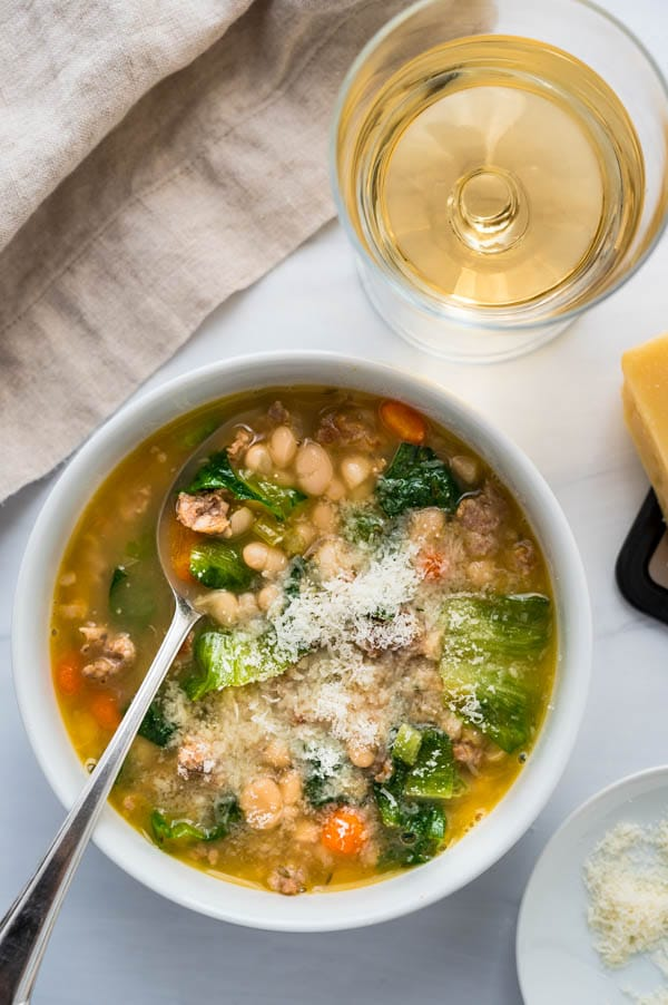 Serving white bean soup with sausage and escarole with a glass of wine and parmesan cheese.