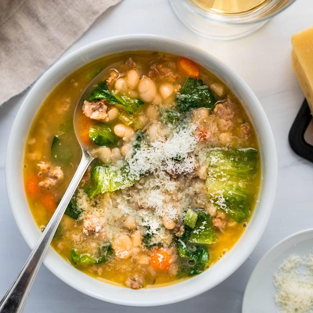 a bowl of navy bean sausage and escarole soup.