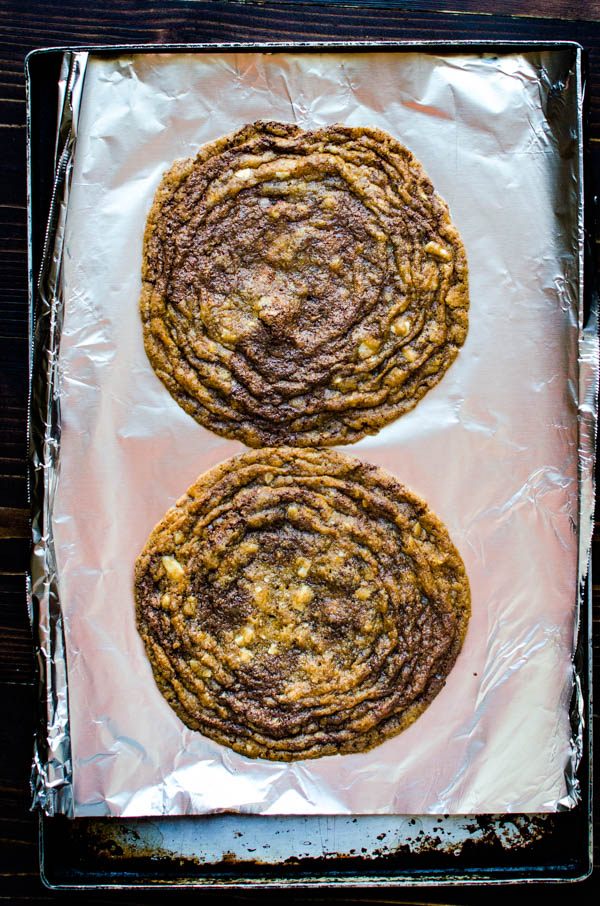 2 Giant Chocolate Chip Cookies on a sheet pan after baking.