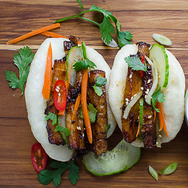 Bulgogi Pork Belly Bao on a wood board.