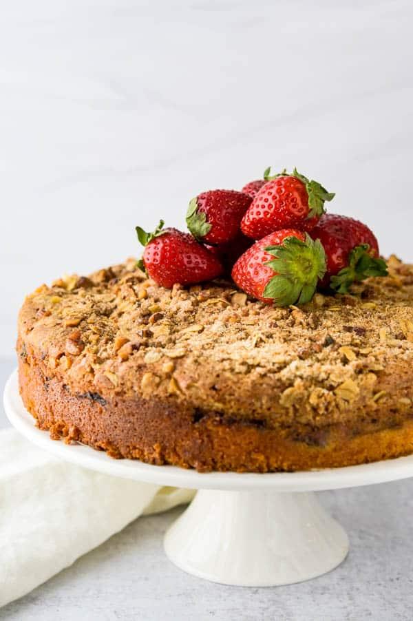 garnishing the lemon crumble cake with fresh strawberries.