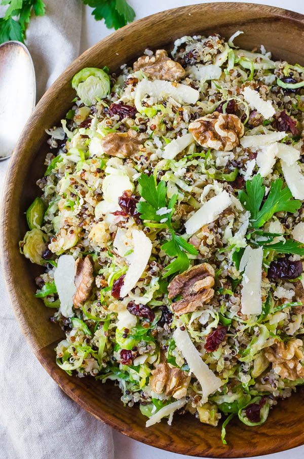 Serving the raw brussels sprouts cranberry quinoa salad in a wooden bowl.