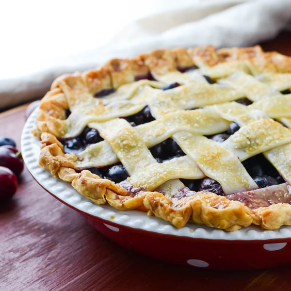 Summer Cherry Berry Pie on red board.