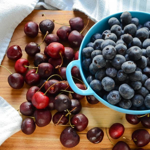 cherries and blueberries on a cutting board.