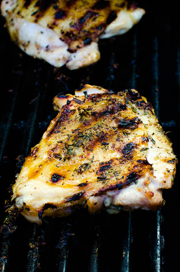 Grilled chicken thighs with spice rub on the grill.