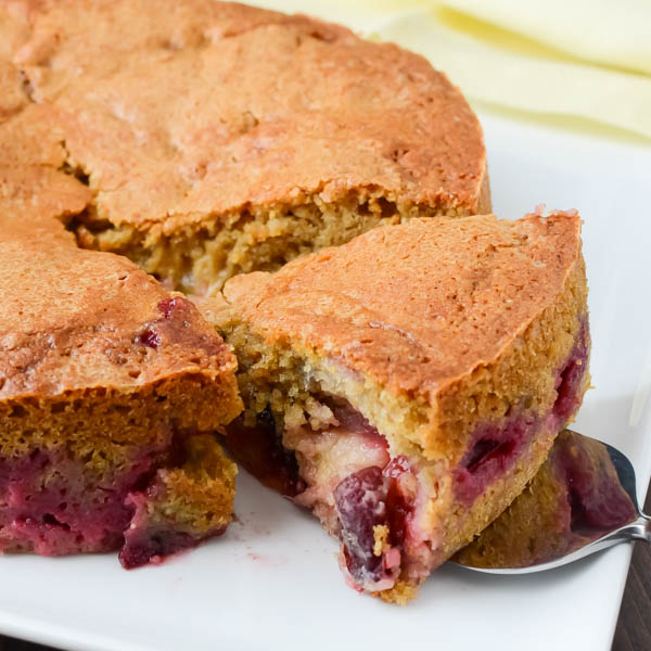 cutting Brown Sugar Cornmeal Plum Cake.