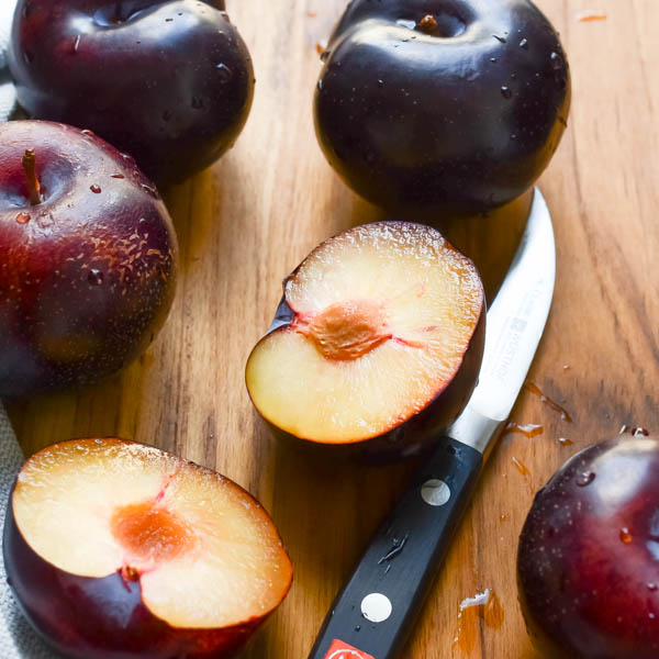 plums with a knife