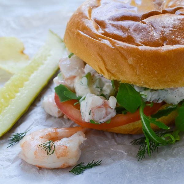 Backlit shot of Easy Poached Shrimp Salad Sandwich with pickle.