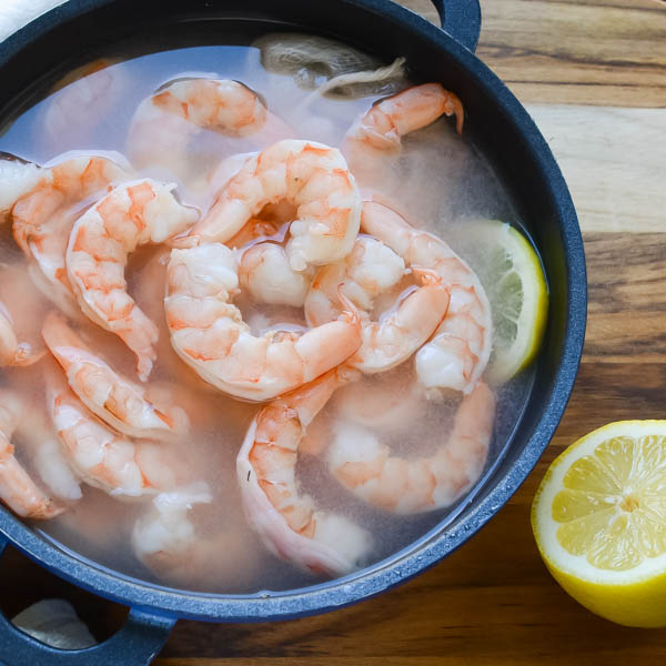 Cooked shrimp in a pot with lemon.