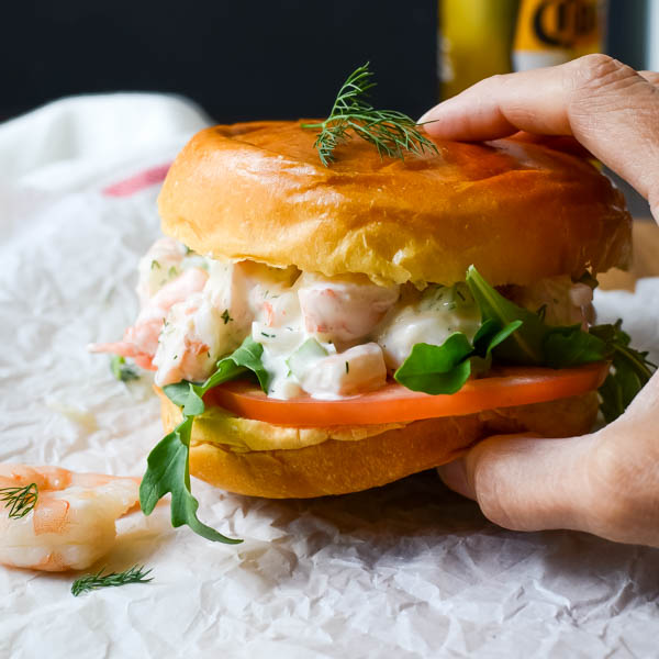 Holding a Easy Poached Shrimp Salad Sandwich.