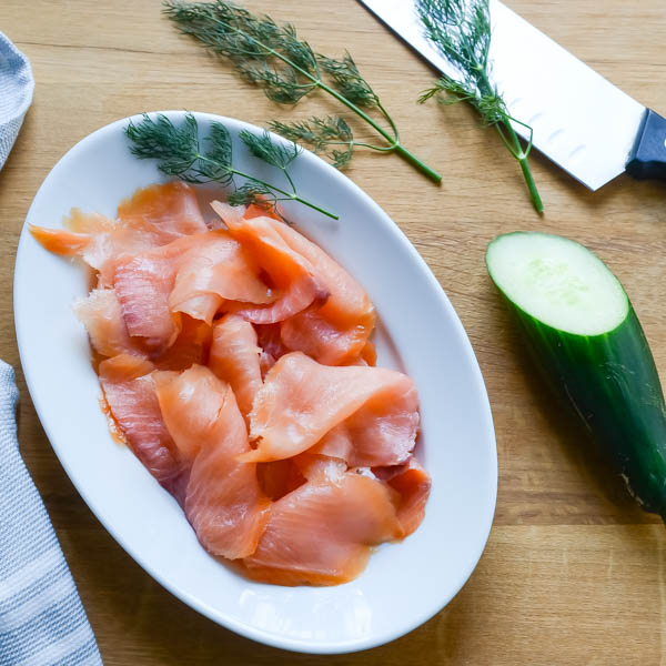 smoked salmon, cucumber and dill on a cutting board.