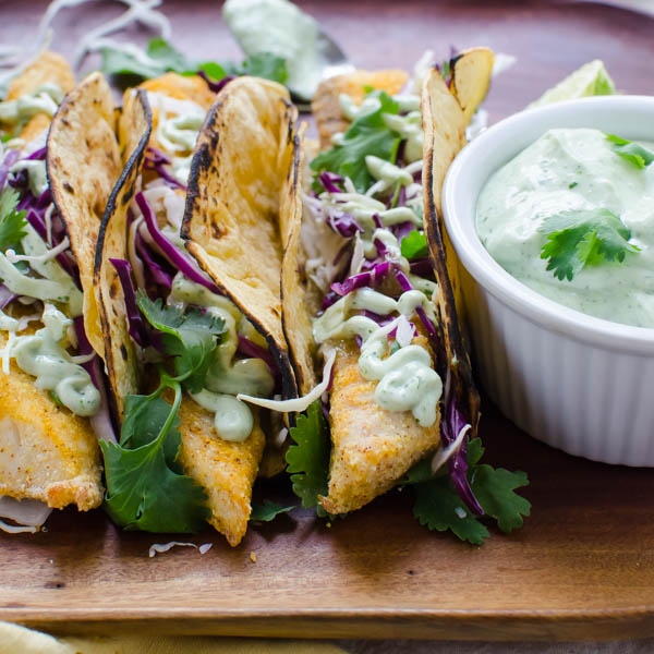 Crispy Baked Fish Tacos on a platter with creme