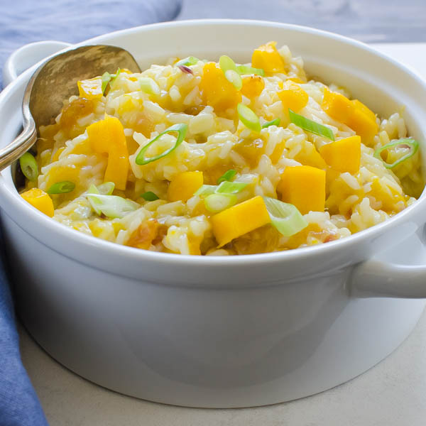 Creamy Coconut Mango Rice in a dish with spoon