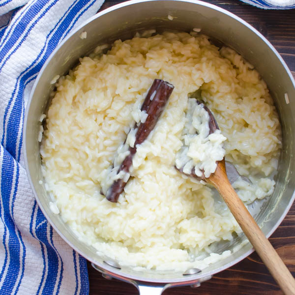 rice and cinnamon stick in pot with spoon