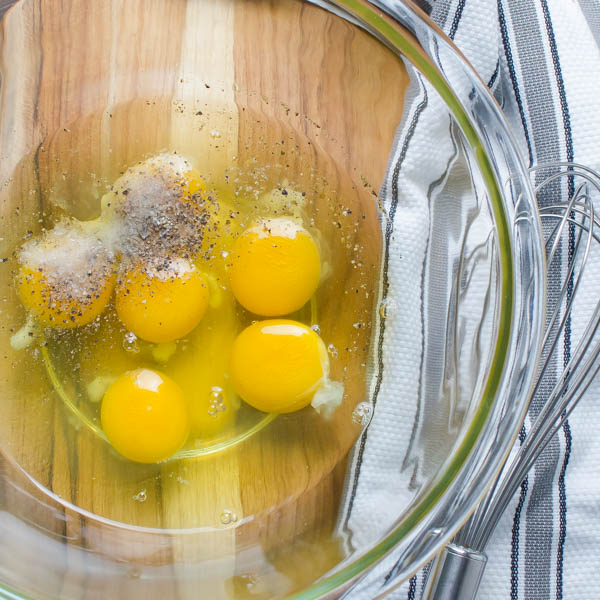 eggs, salt and pepper in a bowl with a whisk.