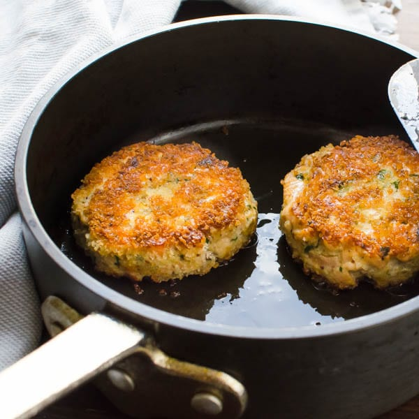 frying salmon cakes in a pan.