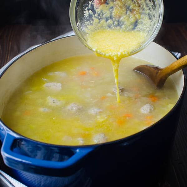Drizzling cheese mixture into soup