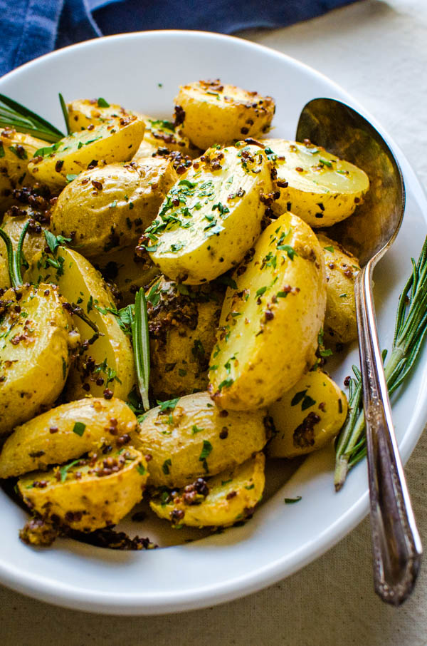 Serving Garlic Herb Mustard Potatoes pot a dish with extra rosemary and a serving spoon.